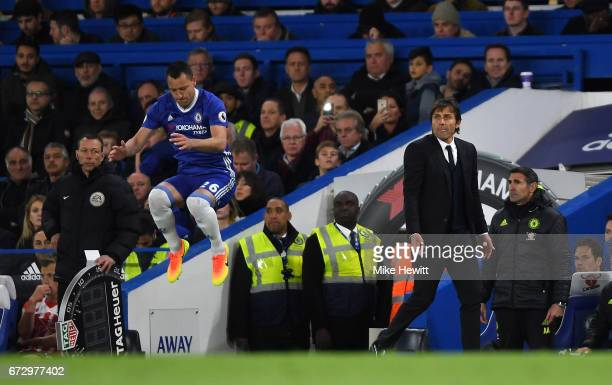 Substitute John Terry of Chelsea warms up as Antonio Conte manager of Chelsea looks on during the Premier League match between Chelsea and...