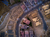 Top down aerial shot of suburban tract housing under construction near Santa Clarita, California. The houses vary in completion from a bare foundation to half tiled roofs.