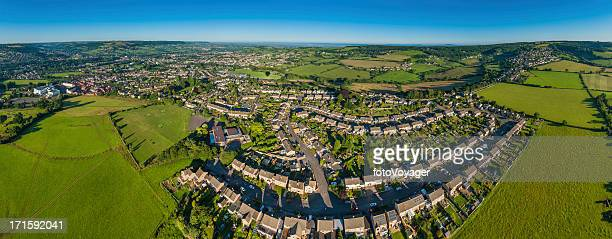 Suburban homes green fields blue skies aerial panorama