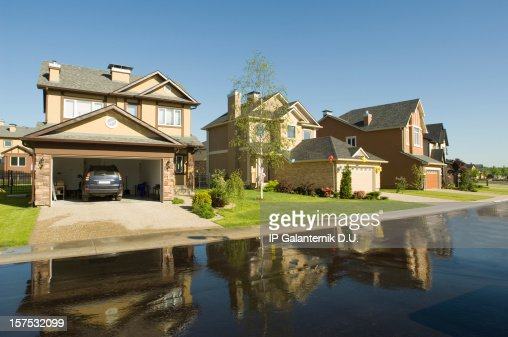 Suburban houses reflected in wet driveway.