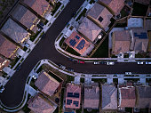 Top down aerial shot of suburban tract housing near Santa Clarita, California. Around twenty single family homes, some with solar panels on the roof.