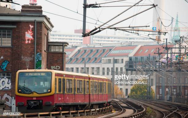 A suburban SBahn train operated by national railway operator Deutsche Bahn pulls into a station in downtown Berlin on November 5 2014 on the start of...