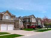 Typical street in a North American upper middle class suburb with large detached homes.