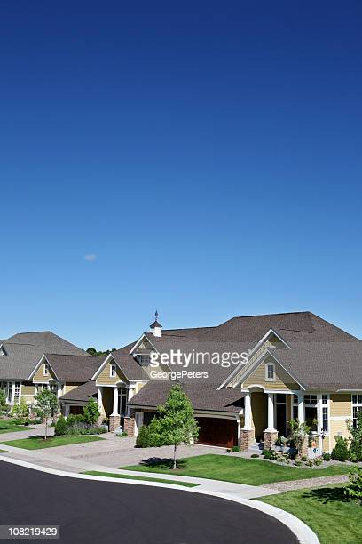 Suburban Street with Manicured Green Lawns and Blue Sky