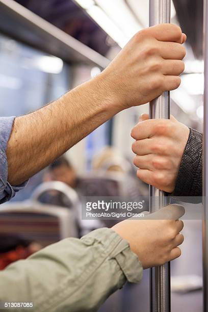 Subway commuters holding onto grab handle