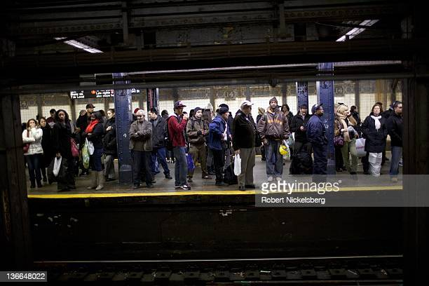 Subway passengers wait on a platform for a New York City subway December 23 2011 in Times Square In 2010 New York's subway system delivered over 16...