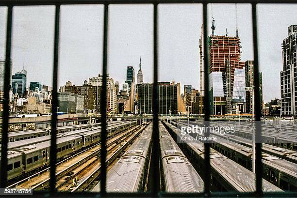 Subway train carriages line up near Hudson Yards station in New York USA and are seen through bars on a fence with a view of New York city buildings...