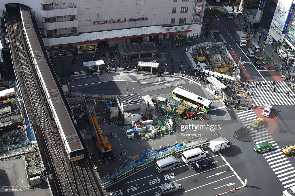 A subway train, left, departs from a station while traffic moves along a street in the Shibuya district of Tokyo, Japan, on Thursday, Nov. 29, 2012. Japan's cabinet approved a second round of fiscal stimulus worth 880 billion yen ($10.7 billion) using budget reserves as Prime Minister Yoshihiko Noda attempts to boost the economy before elections on Dec. 16. Photographer: Kiyoshi Ota/Bloomberg via Getty Images