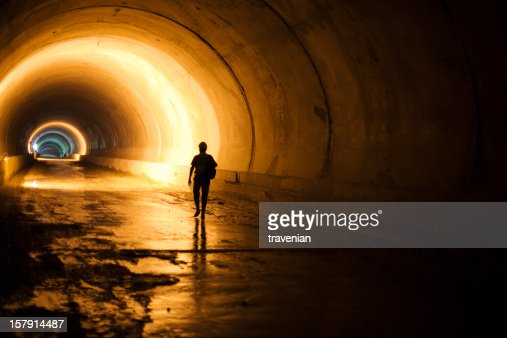 Subway tunnel construction with silhouette of walking worker