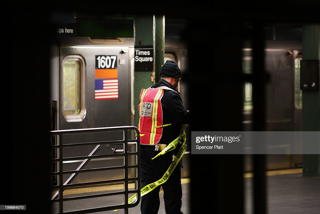 A subway worker removes police tape after an apparent suicide at a subway station in Times Square on January 22, 2013 in New York City. New York City has been experiencing a rash of high-profile incidents involving individuals being hit by trains in suicides, accidents and people being pushed to their deaths.