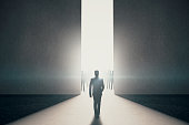 Back view of businessman walking towards abstract opening with bright light and people silhouettes in concrete interior. Success concept. 3D Rendering