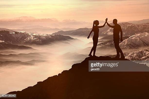 Success men and woman on the mountain