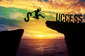 Silhouette man holding S text while jumping over precipice between two mountain and Success text, Success concept, Risk.