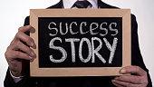 Success story written on blackboard in businessman hands, start new business