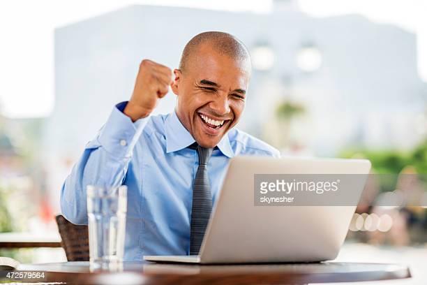 Erfolgreiche afrikanische amerikanische Geschäftsmann mit laptop in einem Café.