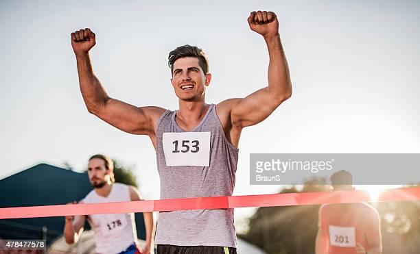 Erfolgreiche Sportlerin Überqueren der Ziellinie und gewinnt das Rennen.