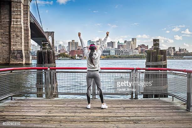 Successful athlete on boardwalk by Brooklyn Bridge