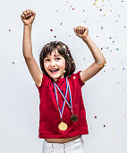Successful beautiful child laughing with champion medals, raising arms for fun victory, celebration and happiness over a confetti background