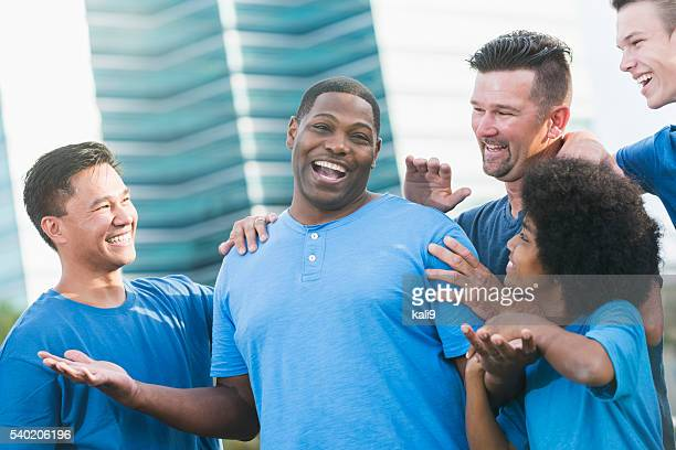 Successful black man getting pat on back from friends