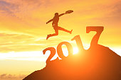 successful business in 2017 new year, business man run and jump on the top of mountain