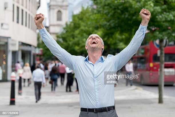 Successful business man celebrating outdoors