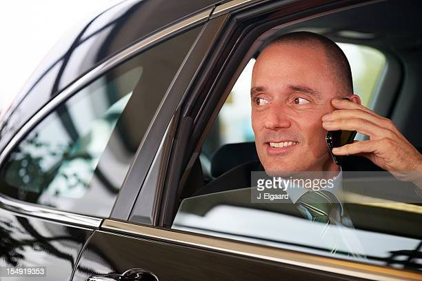 Successful business man on mobilephone in car