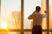 Rear view of handsome young businessman standing in confident pose at window in his office and talking on mobile phone while looking at dawn city scenery in panoramic window. Copyspace