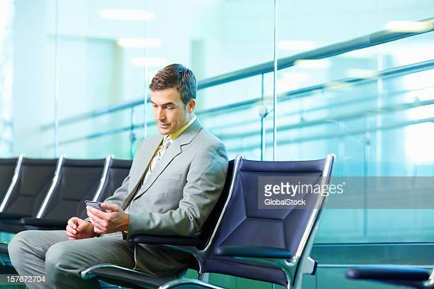 Successful business man reading text message at airport