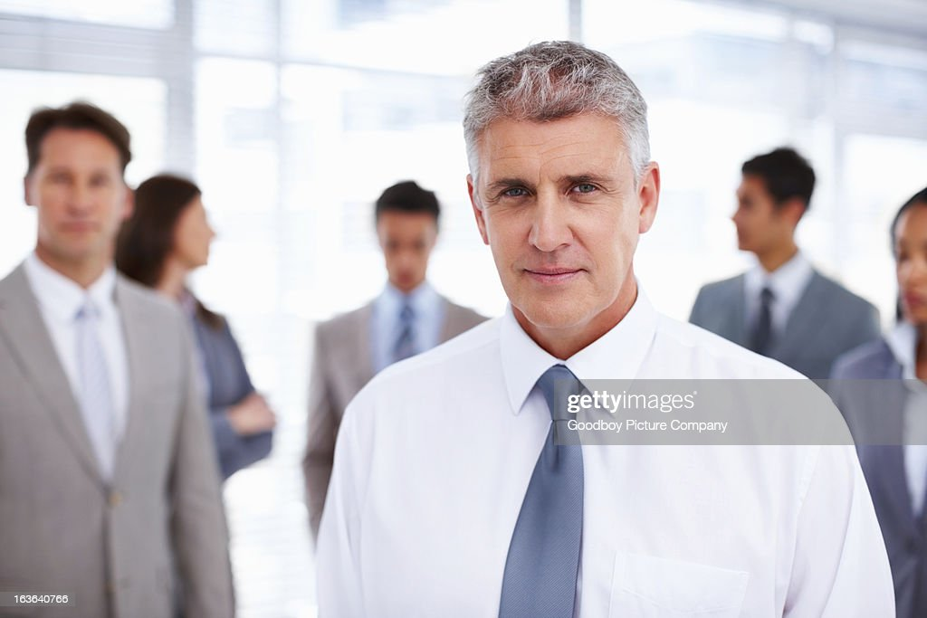 Successful business man with colleagues in office : Stock Photo