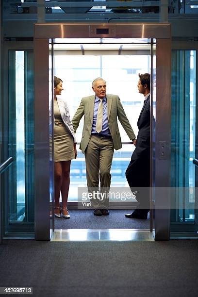 Successful business people standing in office elevator