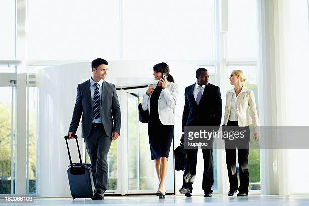 Les voyageurs d'affaires marchant au succès de l'aéroport à l'arrivée