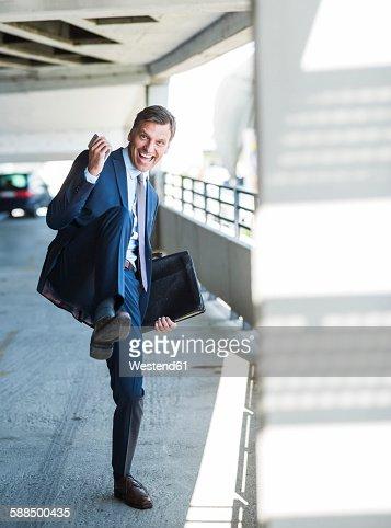 Successful businessman cheering on park deck