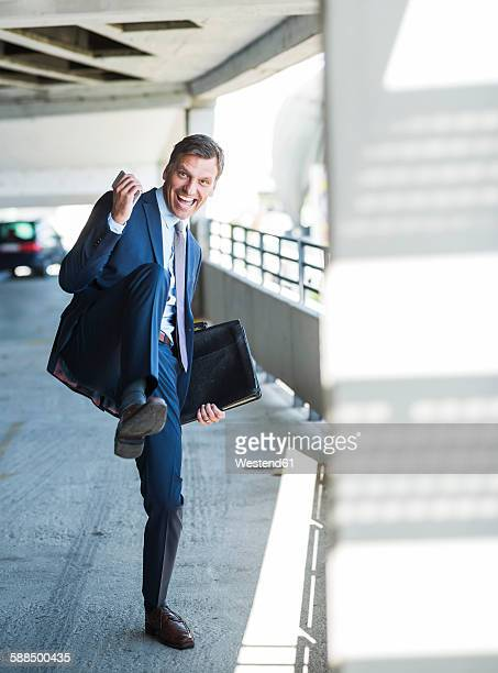Successful businessman cheering on park deck