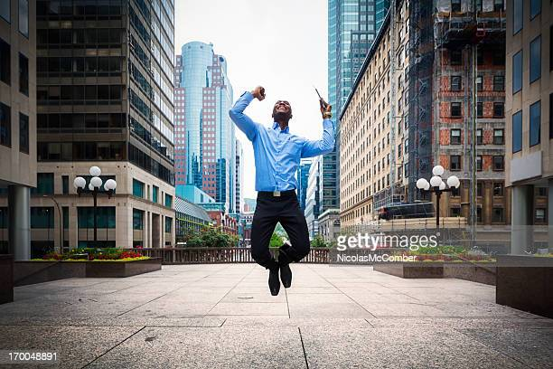 Successful Businessman jumps with joy Downtown Montreal