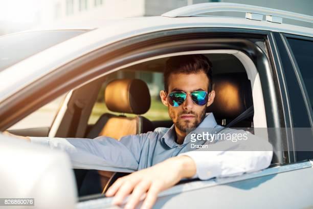 Homme d'affaires prospère, debout sur les feux de circulation dans sa nouvelle voiture