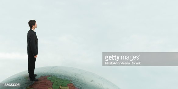 Successful businessman stands on top of the world : Stock Photo