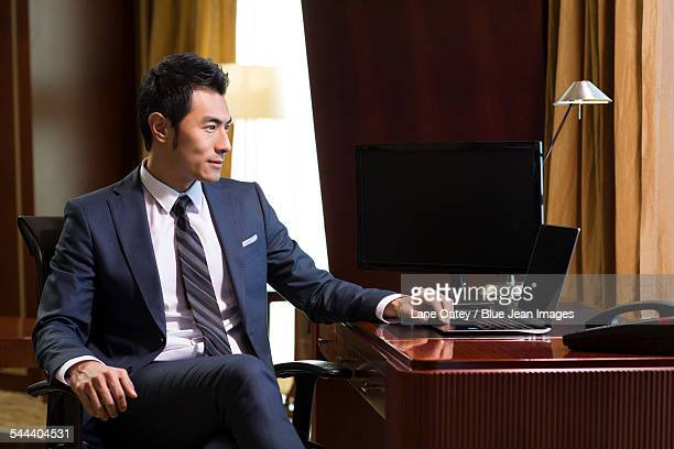 Successful businessman using laptop in study