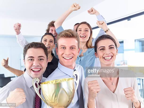 Erfolgreiche Geschäftsleute feiert mit den Pokal in den Händen
