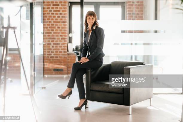 Successful businesswoman sitting on armchair