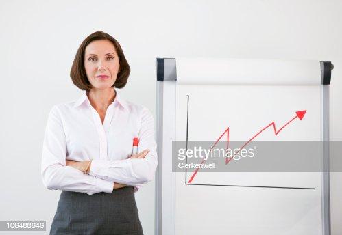Successful businesswoman standing by line graph : Bildbanksbilder