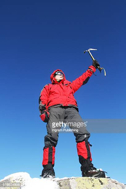 Successful climber with ice axe on top of mountain