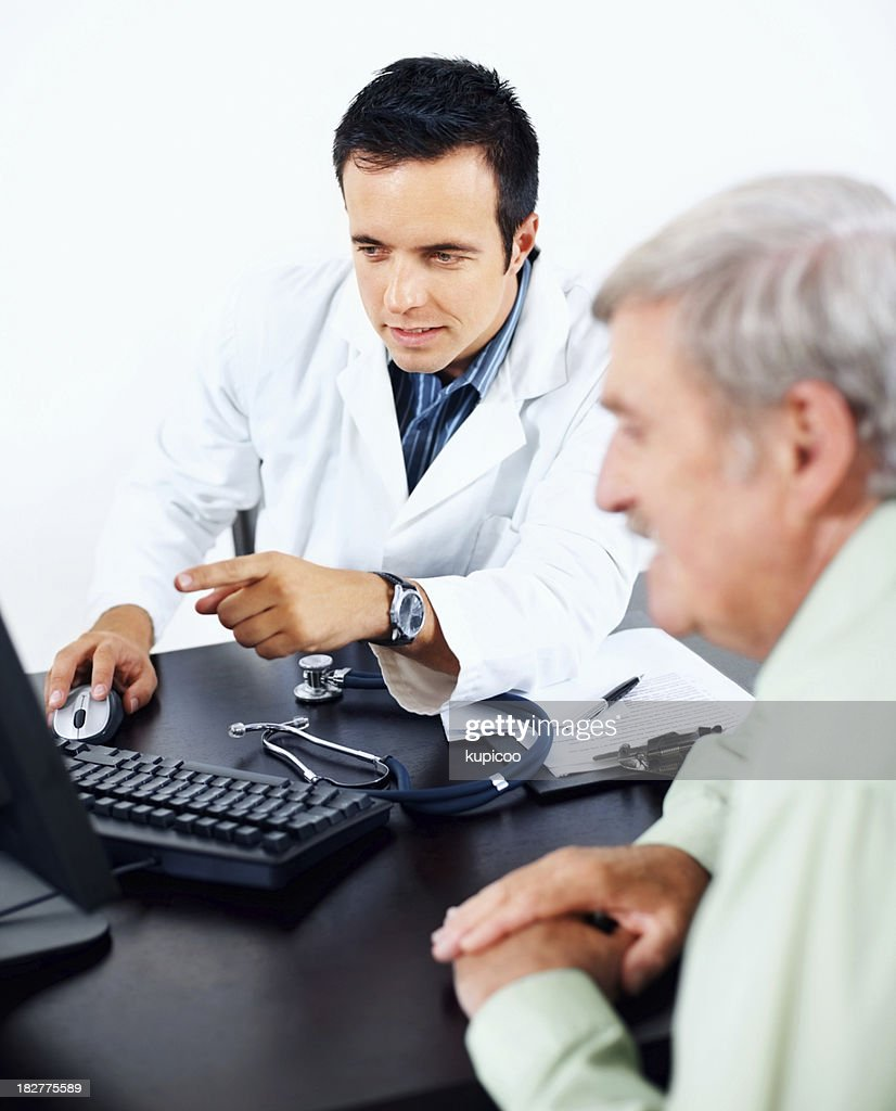 Successful doctor sitting with a patient and computer : Stock Photo