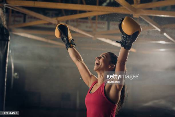Successful female boxer celebrating her victory in a health club.