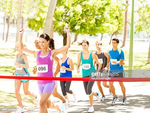 Successo femminile Corridore di maratona attraversando linea del traguardo