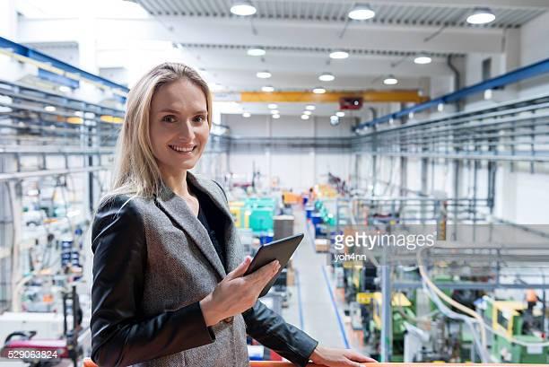 Femme réussi avec une tablette dans le quartier futuriste de plantes