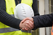 Construction worker and architect shaking hands at construction site