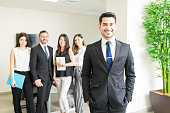 Handsome young CEO leading multiethnic team in office
