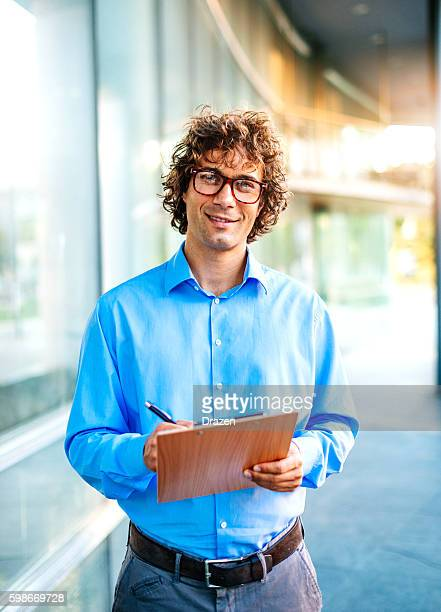 Successful manager smiling near his corporation headquarters