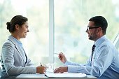 Positive businessman and businesswoman during negotiations