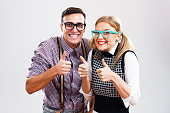 Happy nerdy couple showing thumbs up.